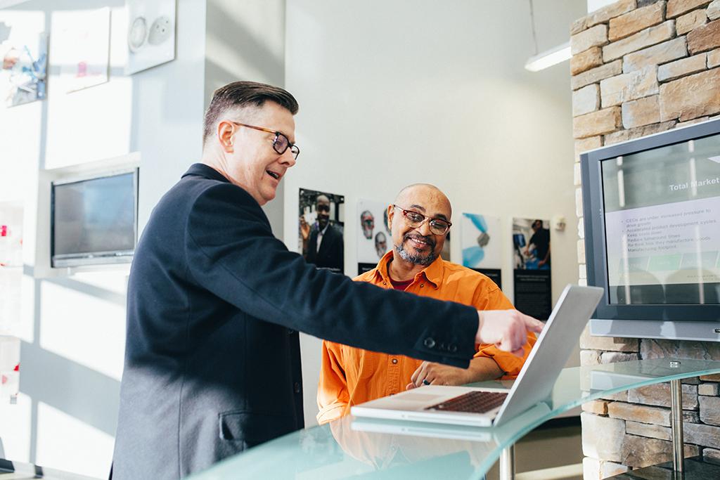 Vendeur qui explique quelque chose à son client sur un portable