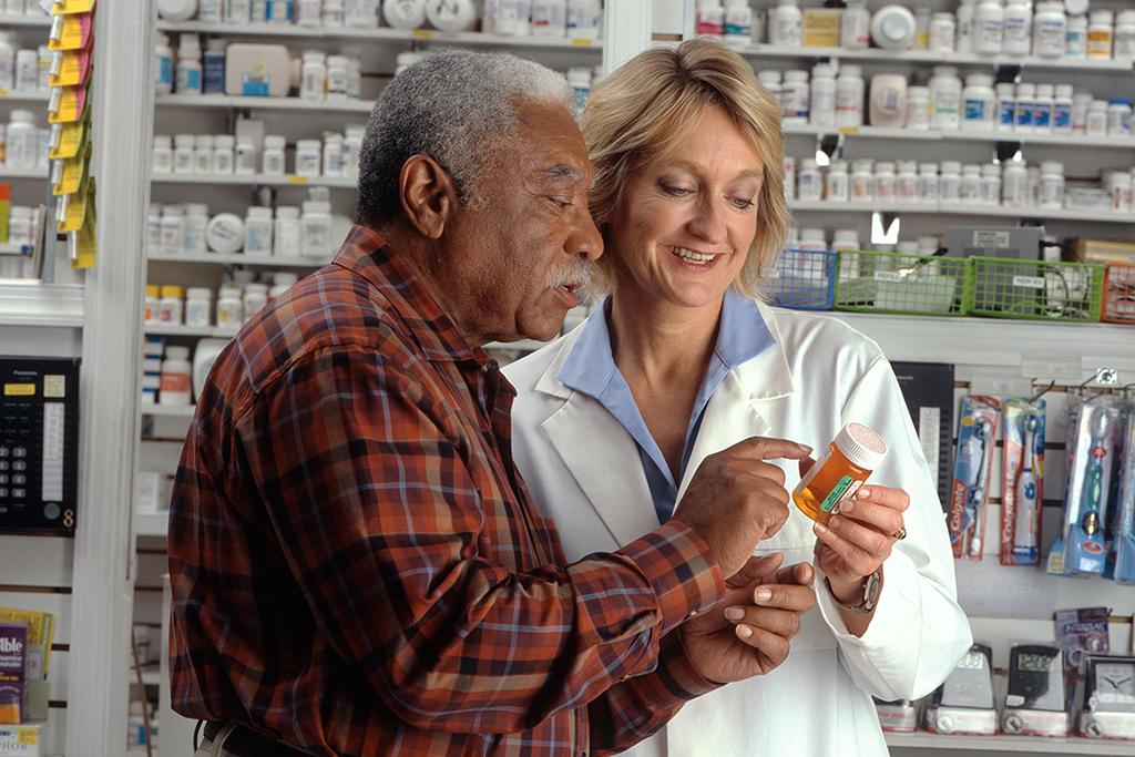 Pharmacienne qui montre un médicament à son client âgé