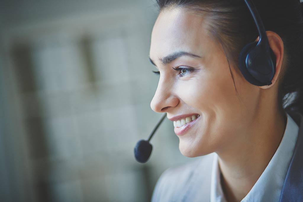 Jeune femme souriante en centre d'appel
