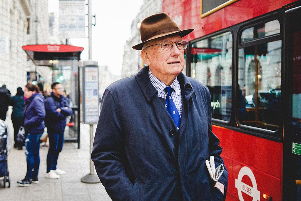 Homme âgé qui attend un autobus