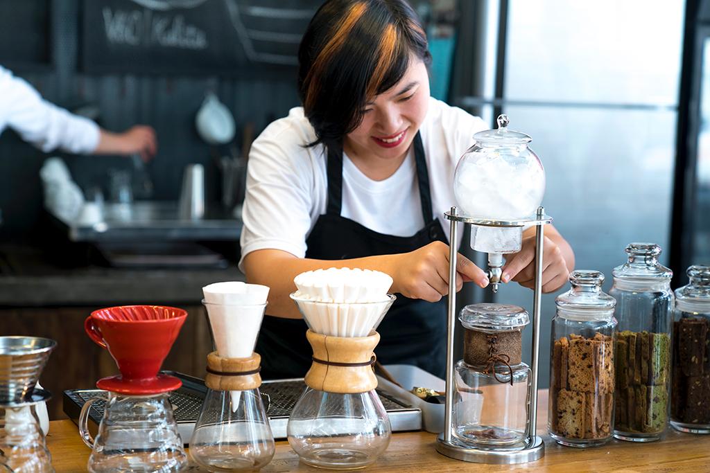 Femme qui prépare un café pour un client
