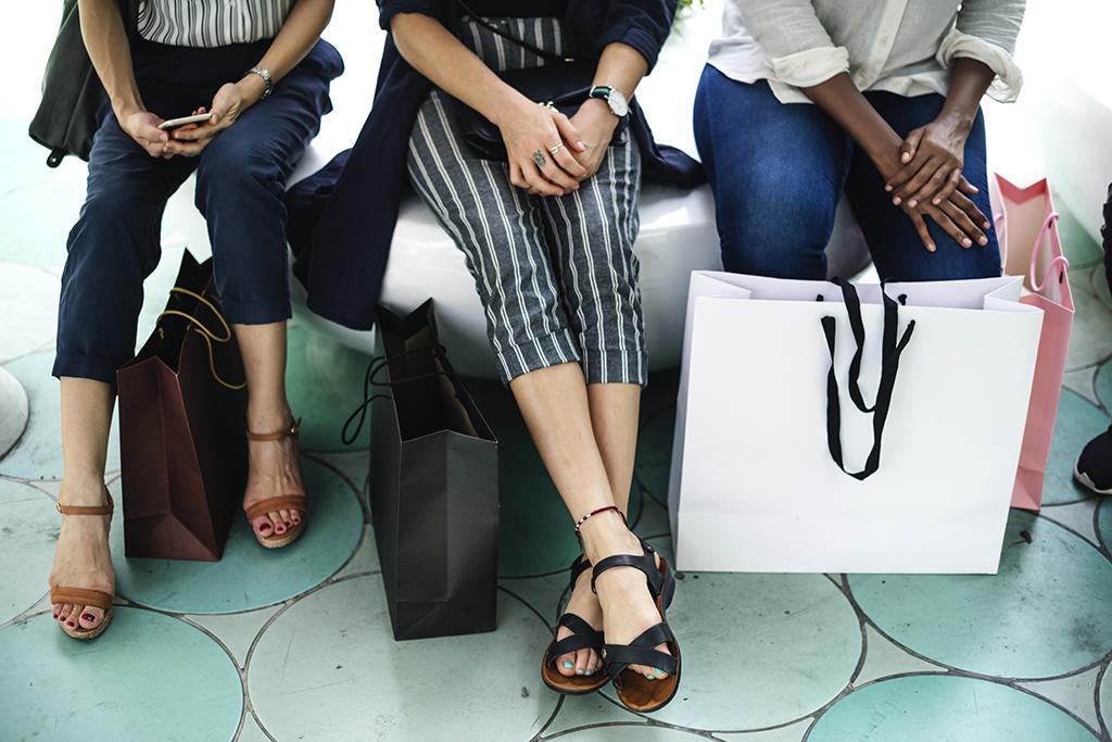 Trois femmes assises avec des sacs de magasinage