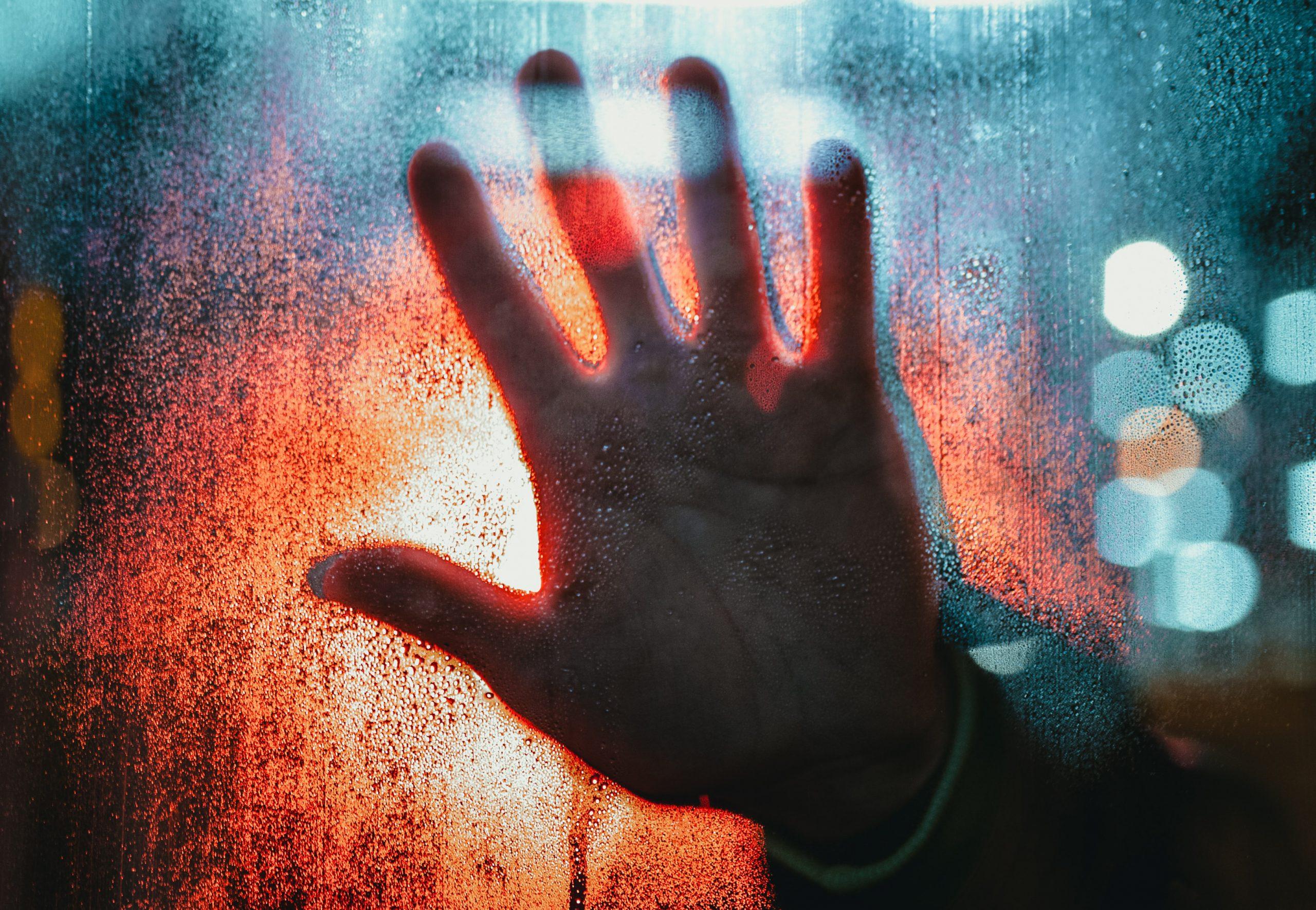 Main derrière une fenêtre en signe d'arrêt